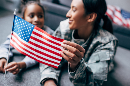 african american daughter and mother in military uniform with american flag at home