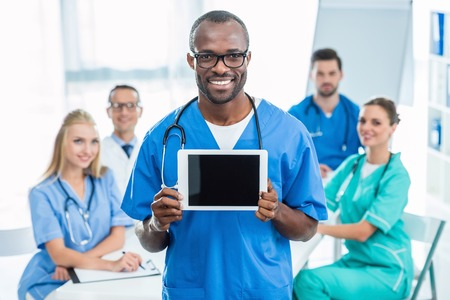 handsome african american doctor holding tablet with colleagues sitting at table on background