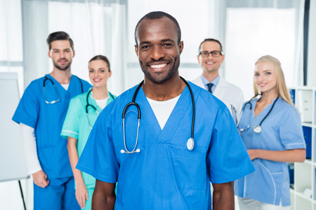 handsome african american doctor with colleagues standing together on background Stockfoto