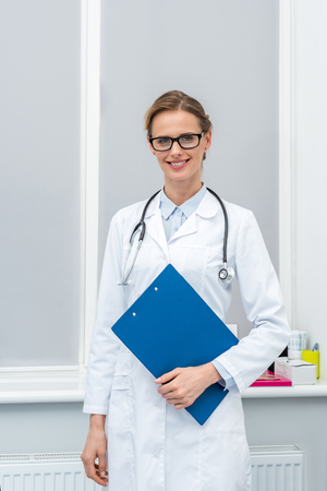 young female doctor with clipboard looking at camera Stock fotó - 102655391