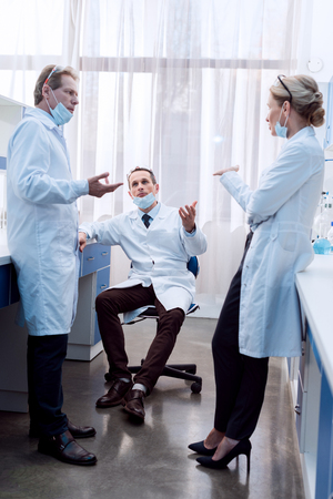 Three medical workers in lab coats and sterile masks discussing work in laboratory Фото со стока
