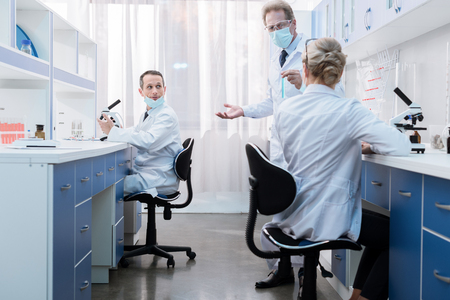 Medical workers in lab coats and protective masks, sitting in laboratory and discussing work