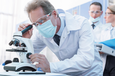 Focused male scientist in white coat and protective gear, working with microscope in chemical lab Zdjęcie Seryjne