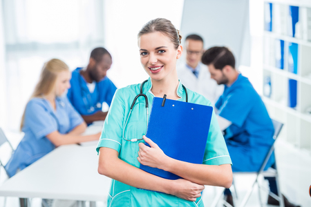 attractive young nurse holding clipboard with colleagues sitting at table on background Stock Photo