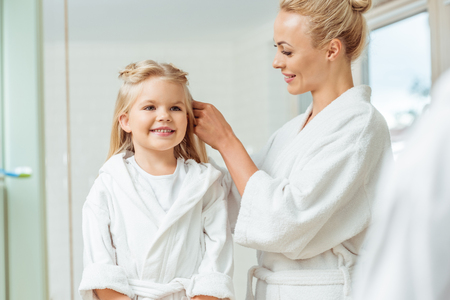 happy mother braiding hair of cute happy daughter in bathroom Stock Photo