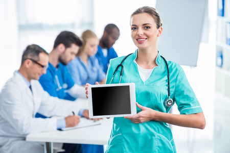 beautiful young nurse holding tablet with colleagues sitting at table on background