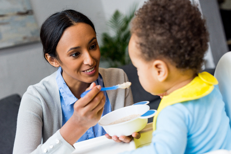 smiling african american mother feeding little son with porridge at home Stockfoto