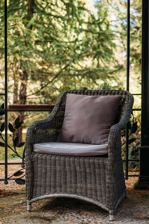 cozy wicker armchair with pillow in alcove