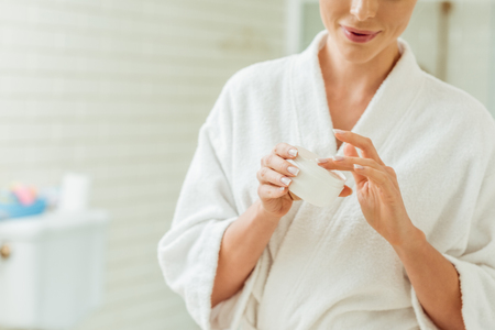 cropped shot of smiling young woman in bathrobe applying face cream Reklamní fotografie