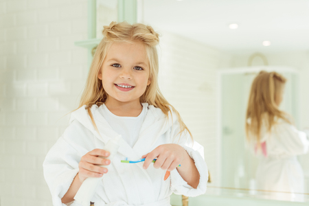 adorable little girl in bathrobe holding toothbrush with toothpaste and smiling at camera Archivio Fotografico