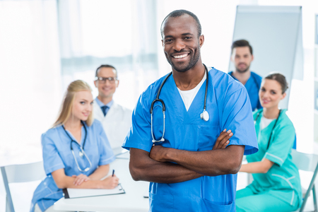 handsome african american doctor with crossed arms with colleagues sitting at table on background Stock Photo