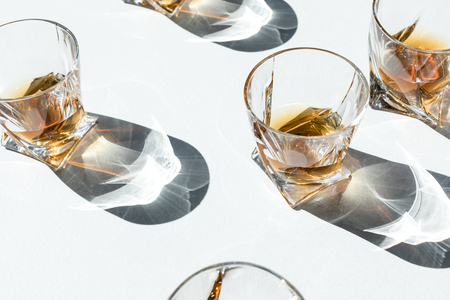 close-up view of luxury cognac in glasses with shadows on white