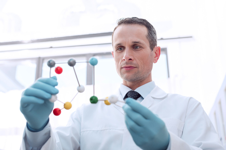 A medical worker in lab coat and latex gloves, examining a molecular model in his hands