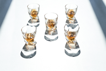 high angle view of whiskey in glasses with shadows on white
