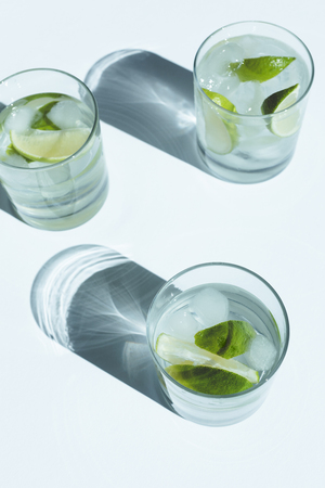 close-up view of Gin Tonic cocktail with lime and ice cubes in glasses