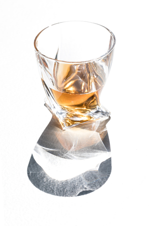 close-up view of whiskey in glass with shadow on white