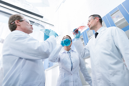 A team of doctors in lab coats pretending to drink from test tubes in chemical laboratory