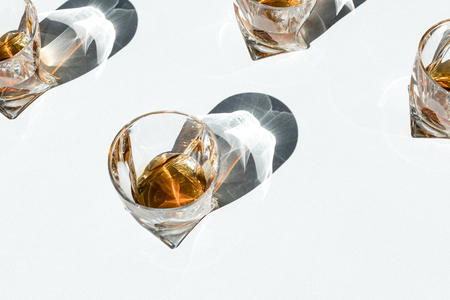 close-up view of cognac in glasses with shadows on white    Banque d'images