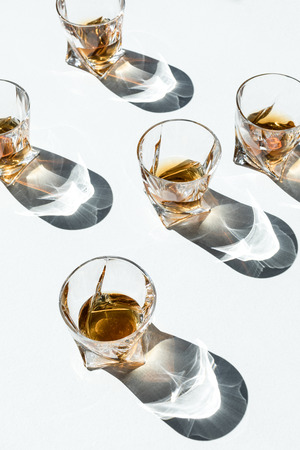 close-up view of luxury whiskey in glasses with shadows on white