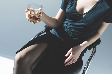 cropped shot of elegant young woman holding glass of whiskey on grey  写真素材