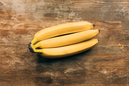 top view of fresh ripe bananas on wooden table