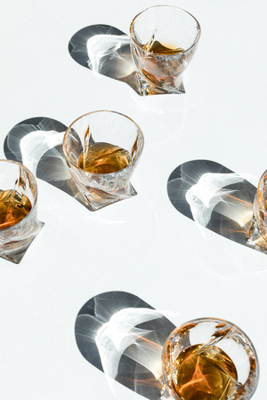 close-up view of whiskey in glasses with shadows on white