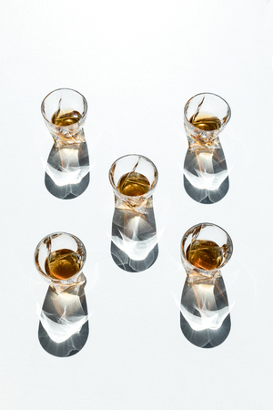 five glasses with brown whiskey and shadows on white Foto de archivo