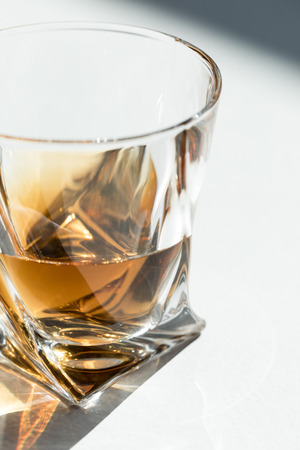 close-up view of cool luxury bourbon in glass on white