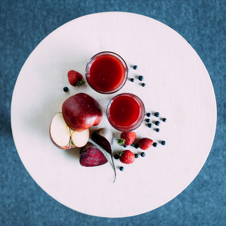 top view of healthy red smoothie in glasses and ingredients