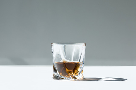 close-up view of whiskey in glass on grey