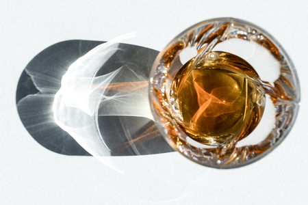 top view of cool whiskey in glass with shadow on white