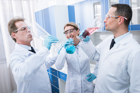 A team of smiling doctors in lab coats pretending to drink from test tubes in chemical laboratory