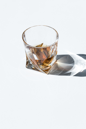 close-up view of whiskey in glass with shadow and copy space on white  Banque d'images
