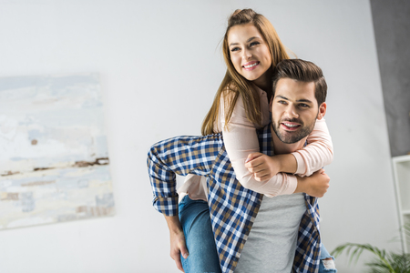 portrait of happy man piggybacking with woman at home