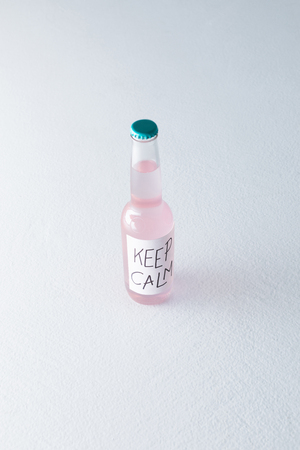 alcoholic beverage in bottle with inscription keep calm on label isolated on grey  Stock Photo