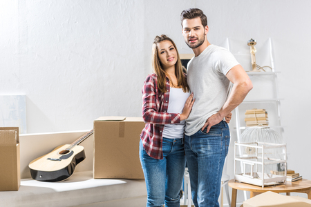 Young attractive couple standing in living room with moving boxes and looking at camera