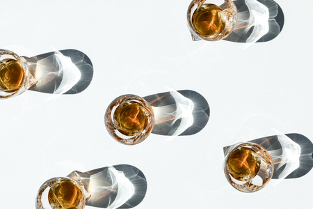 top view of luxury cool whiskey in glasses with shadows on white      Banque d'images