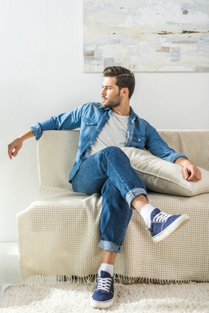 Young attractive man sitting on sofa at home with legs crossed