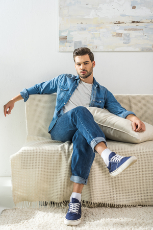 Young attractive man sitting on sofa at home with legs crossed and looking at camera
