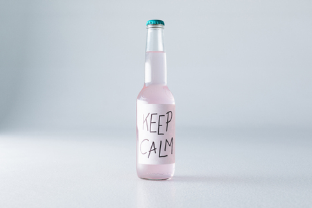 close-up view of alcoholic beverage in bottle with inscription keep calm on label isolated on grey