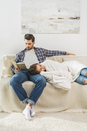 Young man sitting on couch and reading a book, while his girlfriend is napping on his knee Archivio Fotografico - 102612773