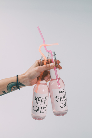 close-up view of bottles of alcohol beverages with straws in hand isolated on grey