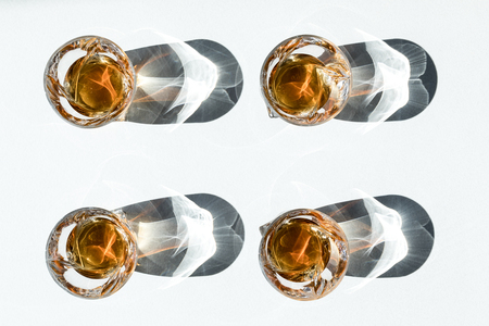 top view of four glasses with luxury bourbon and shadows on white  Foto de archivo