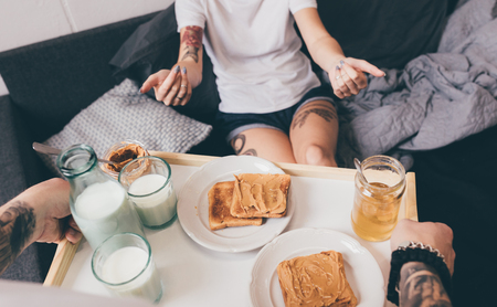 cropped shot of man brought homemade breakfast in bed for girlfriend at home