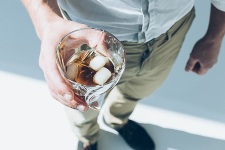 close-up partial view of man holding glass of whiskey with ice cubes