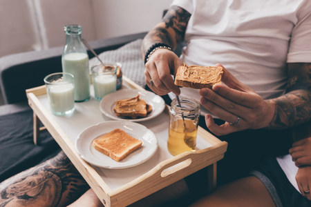 partial view of tattooed man holding toast with peanut butter while having breakfast in bed