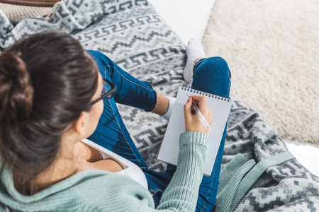 selective focus of young woman writing in notebook at home
