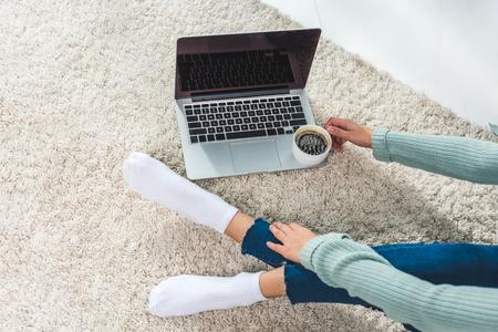 Captura recortada de joven bebiendo café y usando un portátil con pantalla en blanco