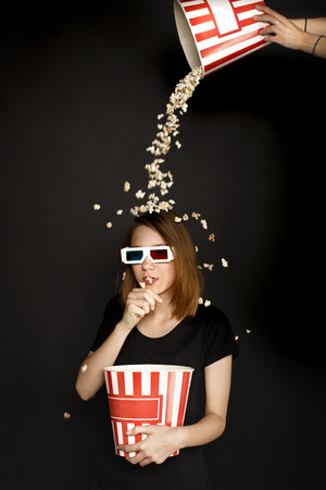 woman with popcorn spilling on her head isolated on black