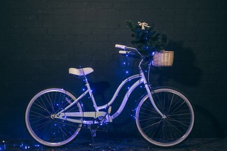 close up view of retro bicycle in christmas lights with christmas tree in basket against black brick wall Stock Photo